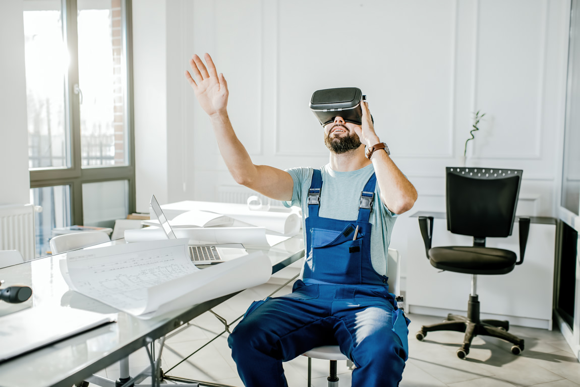 Construction foreman in blue working uniform makes advantage of virtual reality gear to imagine projected environment