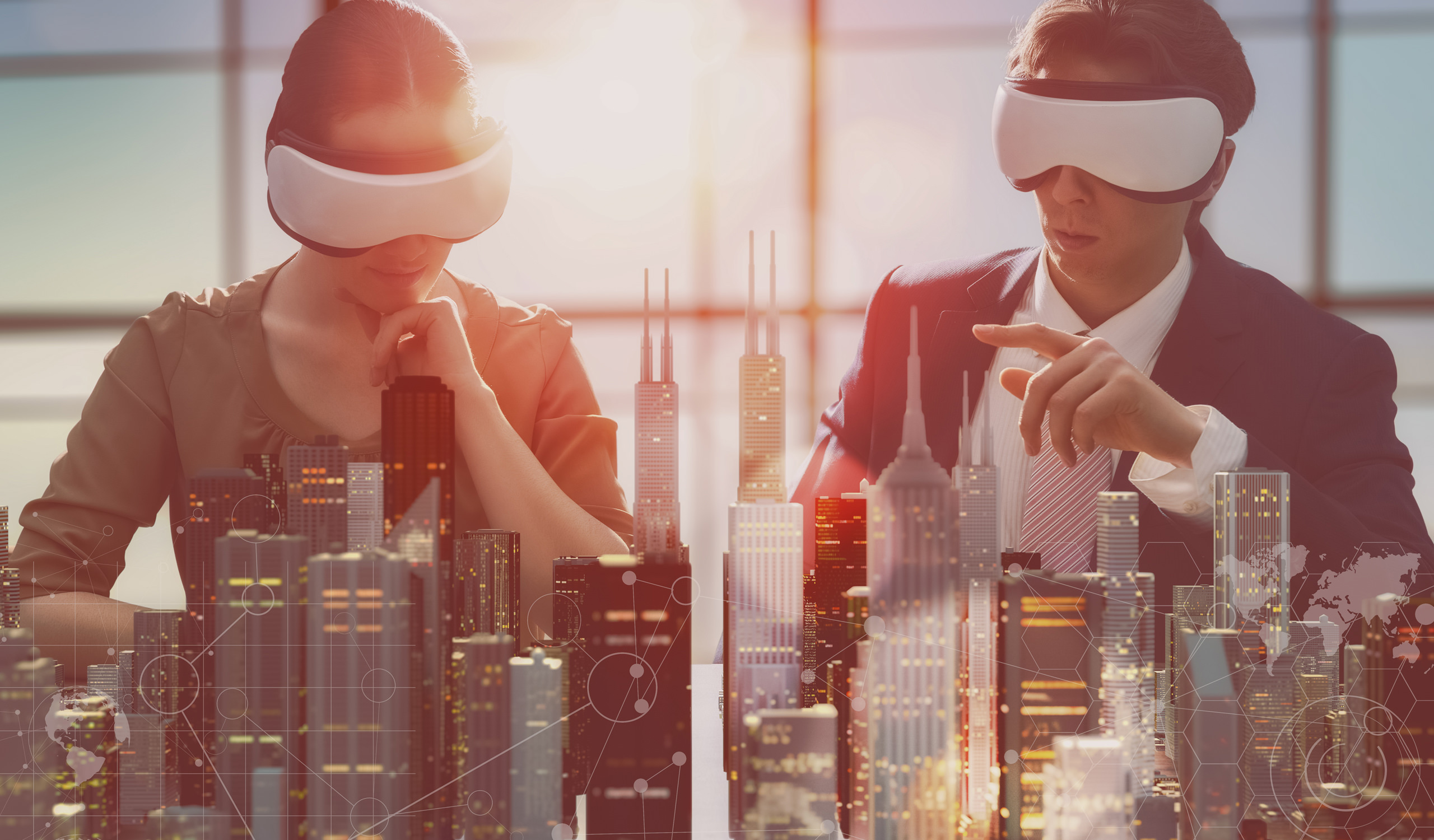 Lunas Visialization Studio creates interactive virtual reality tours for real property and developers markets. Man and woman watching city construction plan with VR glasses in the office