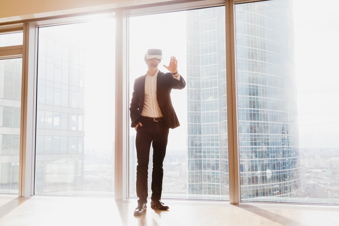 Man with VR goggles looks around office space viewing walkaround 3D tour