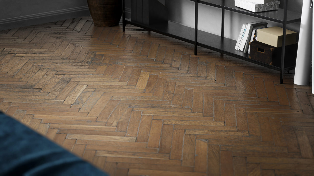 A detailed 3D rendered close-up of the herringbone parquet floor with the shabby chic effect of photorealistic quality